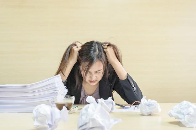 Крупным планом работающая женщина подчеркнуты из кучи рабочей бумаги перед ней в работе