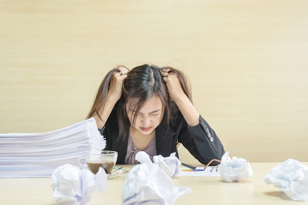 Closeup working woman are stressed from pile of work paper in front of her in work