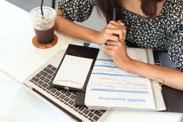 Closeup workspace of insurance broker laptop health insurance information form on desk