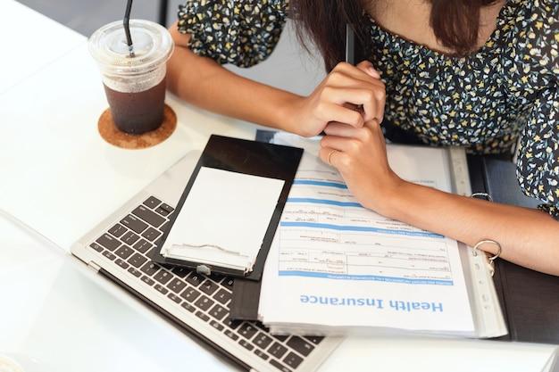 Крупным планом рабочее место страхового брокера, ноутбук, форма информации о медицинском страховании на столе