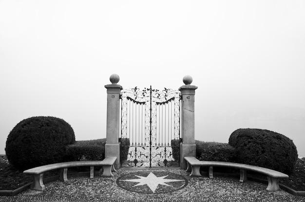 Primo piano di un cancello in ferro battuto con siepi con nebbia in bianco e nero