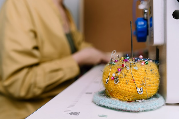 Closeup of yellow needle cushion with a woman working with sewing machine in the back in a workshop