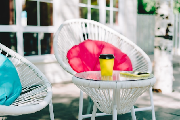 Closeup of a yellow paper disposable cup of coffee on a table in empty cafe without people outside