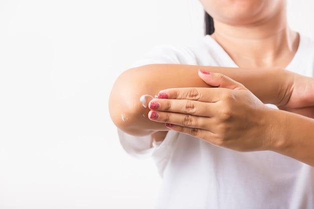 Closeup young asian woman applies lotion cream on her elbow