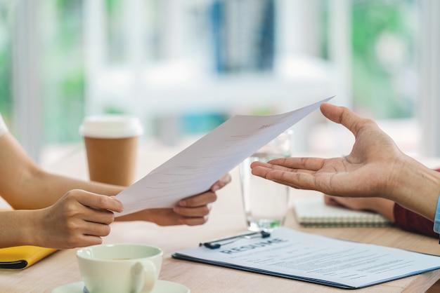 Крупным планом молодая азиатская женщина-выпускник рука и отправка документа резюме