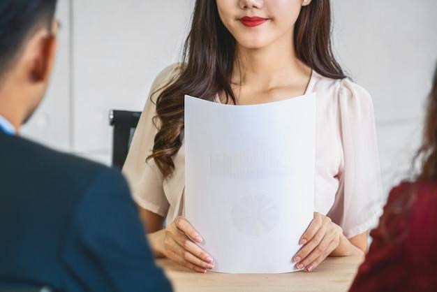Крупным планом молодая азиатская женщина-выпускница держит документ с резюме и готовится к двум менеджерам