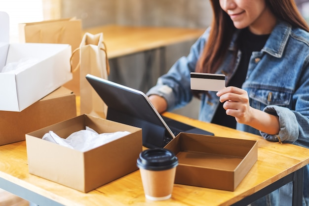 Closeup  of a young asian woman using tablet pc and credit card for online shopping with postal parcel box and shopping bags on the table