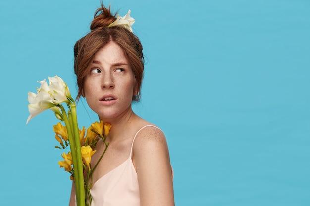 Primo piano della giovane attraente redhead femmina con bun acconciatura sollevando confusamente le sopracciglia mentre guarda pensieroso verso l'alto, isolato su sfondo blu
