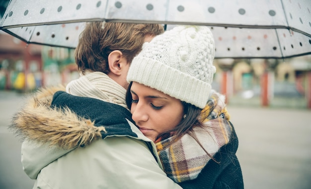 Closeup of young beautiful couple embracing under the umbrella in an autumn rainy day. love and couple relationships concept.