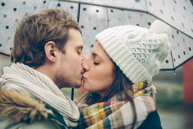 Closeup of young beautiful couple kissing under the umbrella in an autumn rainy day. image focused on the lips.