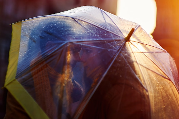 Closeup of young beautiful couple kissing under umbrella