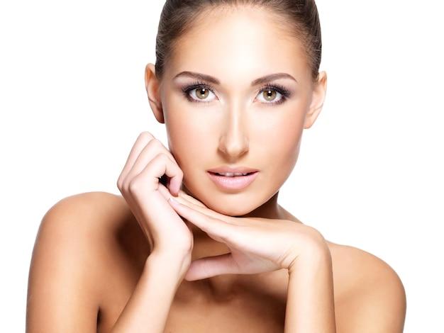 Primo piano di una giovane bella donna con la pelle fresca pulita che tocca il suo fronte