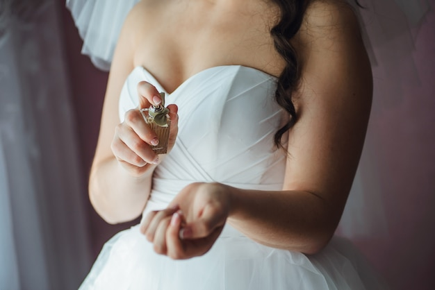 Closeup of young bride getting ready with perfumes at home in the morning on the wedding day