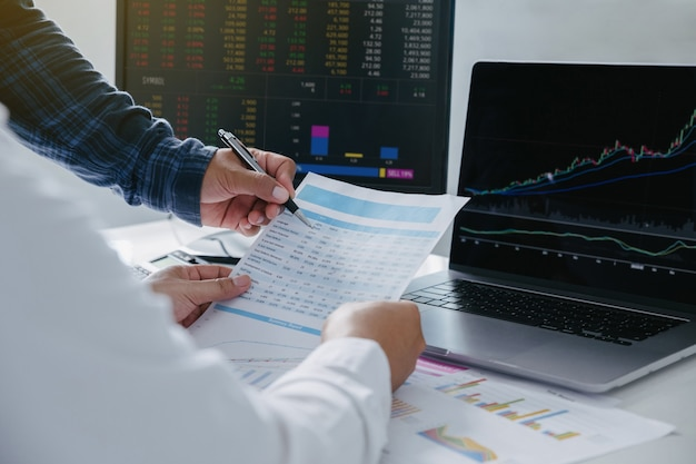 Closeup of young business team investment trading discussion and analysis finance market graph