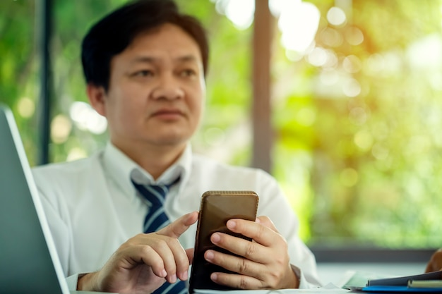 Closeup of young businessman sitting and looking forward in mobile phones to find information