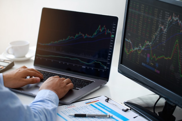 Closeup young businessman statistic graph of stock market financial indices analysis on a laptop