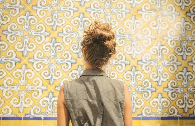 Primo piano di una giovane donna caucasica in top senza maniche con colletto grigio rivolto verso la parete floreale