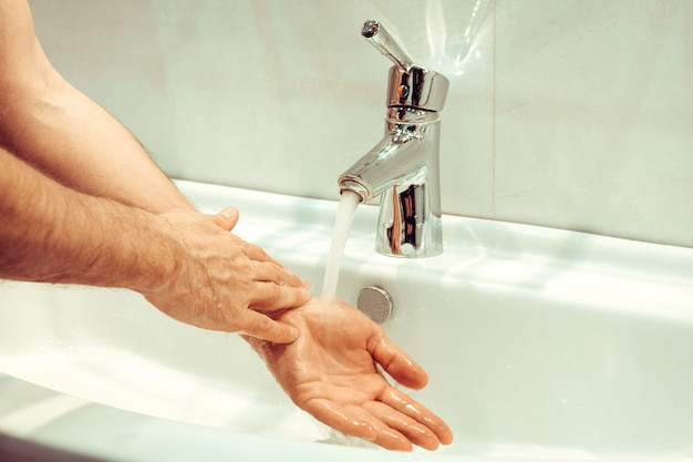 Closeup of young caucasian man washing his hands with soap in the sink of bathroom personal hygiene