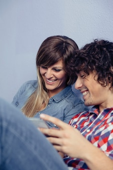 Closeup of young couple in love looking smartphones and laughing while resting over a bed. leisure time at home concept.