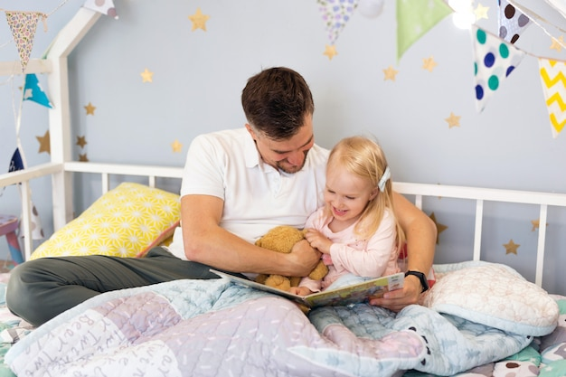 Closeup of young father dad in bed with his happy toddler daughter reading a book