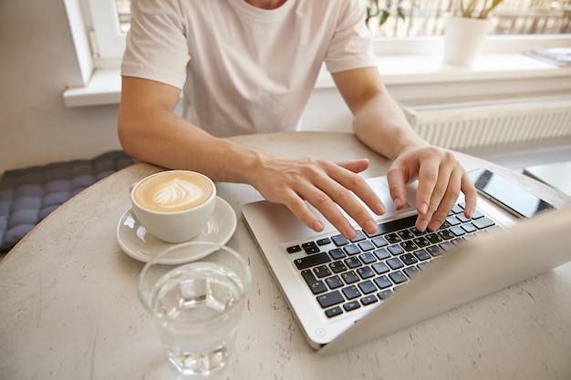Молодой парень крупным планом с руками на клавиатуре, удаленно работая с ноутбуком и смартфоном, пьет кофе в кафе, носит повседневную одежду