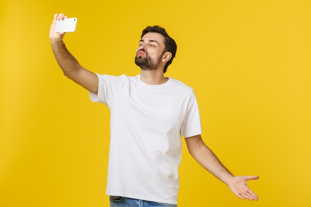 Closeup of young handsome man looking at smartphone and taking selfie. isolate over yellow.