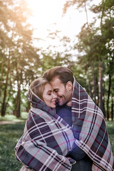 Closeup of young happy couple laughing under blanket in a cold day with autumn forest on the background