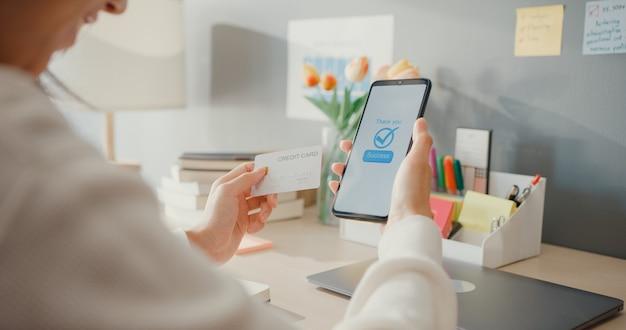 クローズアップの若い女性は、携帯電話の注文オンラインショッピング製品を使用し、家のリビングルームのインテリアでクレジットカードで請求書を支払います。