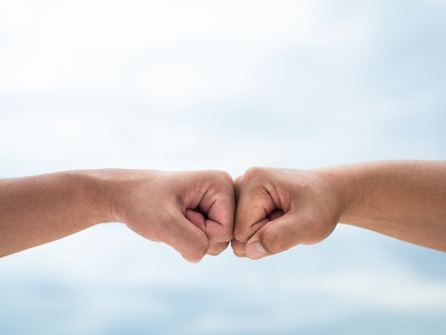 Closeup young man fist bump on the blue sky sea background