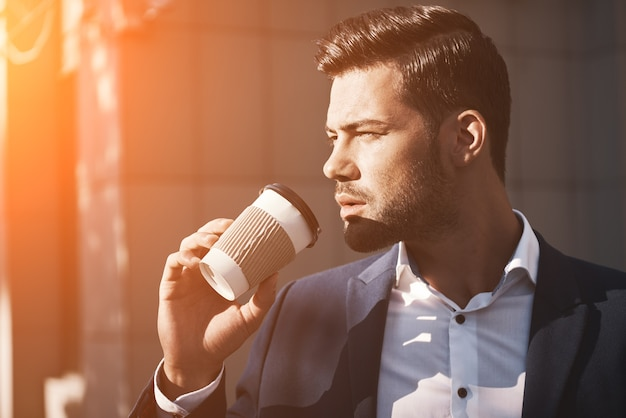 Closeup of young man holding coffee to take away at early morning in sunny park