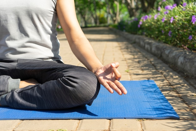 Closeup of young man meditating in lotus pose and practicing hand mudra outdoors