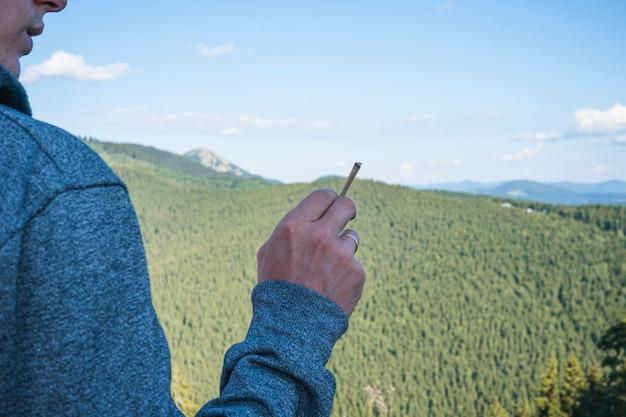 Closeup of young man smoking marijuana joint outdoors hemp blunt in the male hand