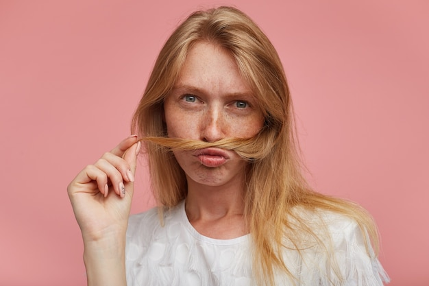Closeup of young pretty redhead female with casual hairstyle imitating mustache with lock of hair and looking seriously at camera, dressed in casual clothes while posing over pink background
