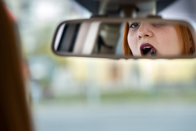 Closeup of a young redhead woman driver correcting her makeup with dark red lipstick looking in car rearview mirror behind steering wheel of a vehicle.