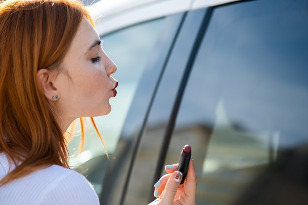 Closeup of a young redhead woman driver correcting her makeup with dark red lipstick looking in car reflective window.
