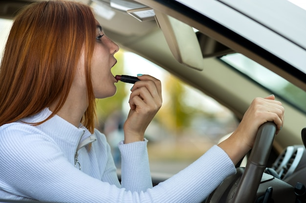 Closeup of a young redhead woman driver correcting her makeup