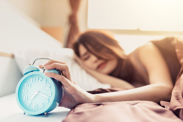Closeup young sleeping woman and rise hand to turn off alarm clock in the bedroom at home