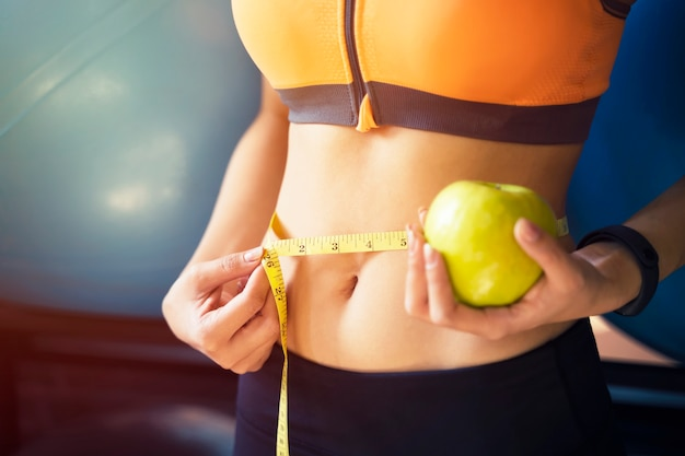 Closeup of young sport woman using measure tape on her abdomen with green apple on her hand