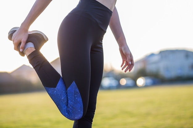 Closeup of young sportive woman doing exercise before running in morning field outdoors.