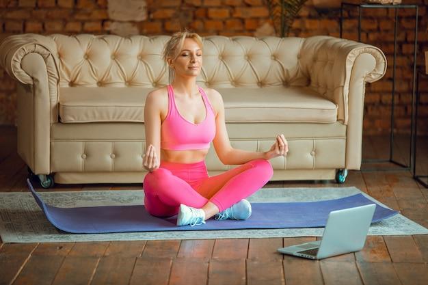 근접 촬영 젊은 스포티 한 슬림 여성 코치는 비디오 온라인 교육 요가 강사 현대 노트북 명상 휴식을 호흡 쉬운 좌석 포즈 건강한 라이프 스타일 개념 스포츠 집에서