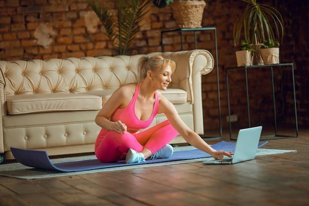 근접 촬영 젊은 스포티 한 슬림 여성 코치는 카메라 명상에 현대적인 비디오 온라인 훈련 요가 강사를 연습 하며 집에서 편안한 좌석 포즈 체육관 건강 한 라이프 스타일 개념 운동