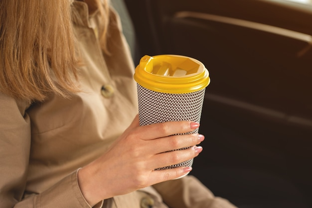 Closeup of a young unrecognizable woman in beige coat holding a cup of hot drink and sitting on the car.