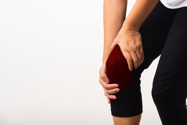 Closeup young woman aches to suffer from pain knee