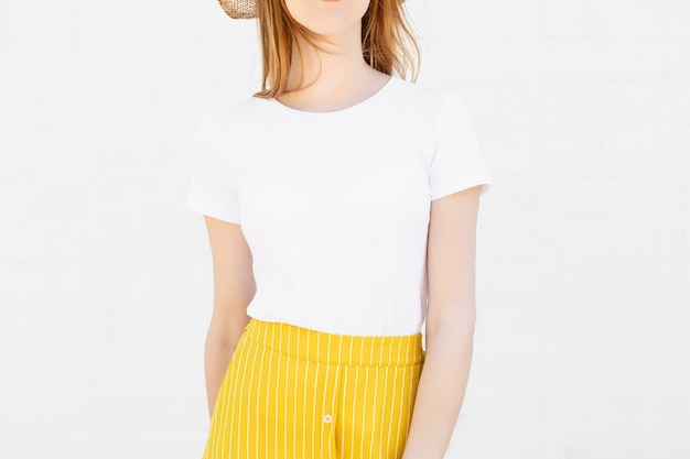 Closeup of young woman in blank white t-shirt and a bright orange skirt