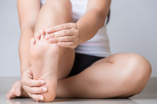 Closeup young woman feeling pain in her foot at home. healthcare concept.