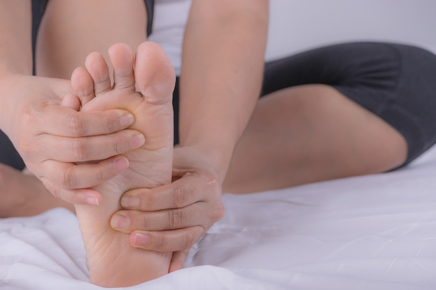 Closeup young woman feeling pain in her foot at home.
