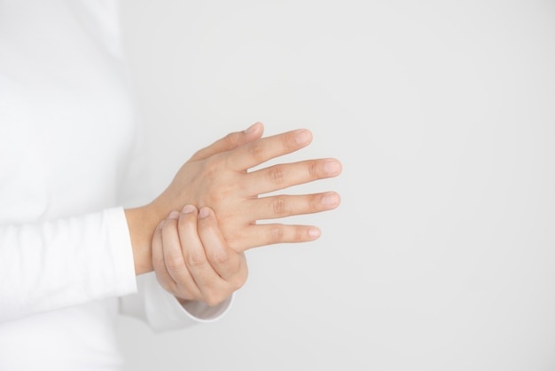 Closeup of young woman holds her wrist, hand injury, feeling pain