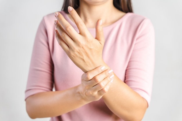 Closeup young woman holds her wrist on white. hand injury, feeling pain. health care and medical concept.