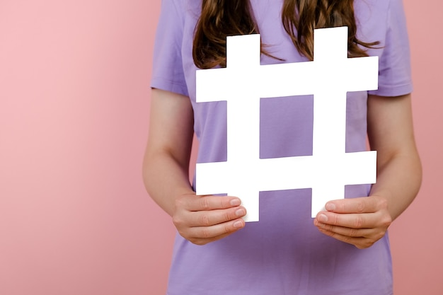 Closeup of young woman holds large big white hashtag sign, concept of trendy social media posts and blogging, viral web content, internet promotion, isolated over pink background wall in studio