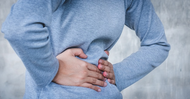 Closeup of young woman is having stomach ache